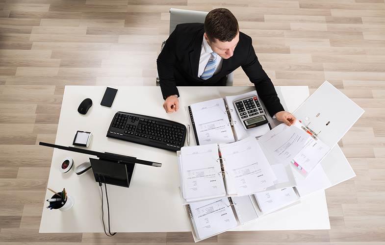 Бизнесмен заполняет бумаги по таможенным сборам